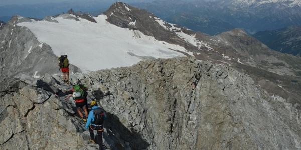Ein hübscher Felsgrat führt zuletzt zum Gipfel des Hochgall. Über dem Rieserferner grüßt der Schneebige Nock.