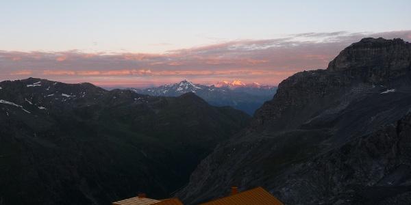 Die ersten Sonnenstrahlen lassen den Piz Bernina aufleuchten