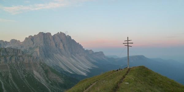 Das Gipfelkreuz des Zendleser Kofels mit den Geislern im Hintergrund
