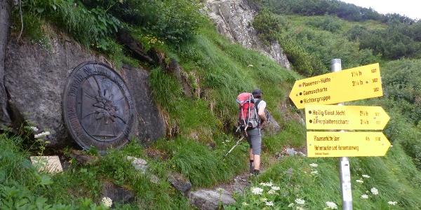 Wegschilder und eine Tafel weisen den Anstieg zur Plauener Hütte.