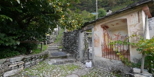 An einem Bildstock beginnt der Treppenweg hinauf zur Kapelle Madonna della Pioda.