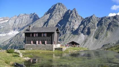 Vor der Kulisse der mächtigen Gipfel von Torrente Alto und Torrente Basso liegt die gemütliche Capanna Cava.