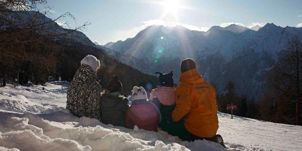Familie sitzt im Schnee