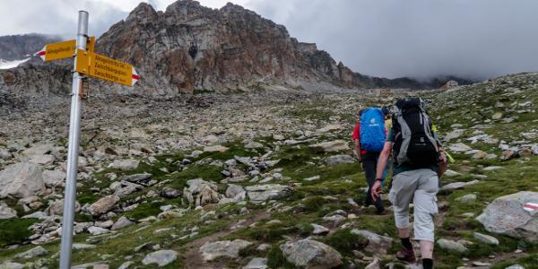 Die Almagellerhütte ist bereits zu erkennen, hinter dem Wegweiser Dri Horlini