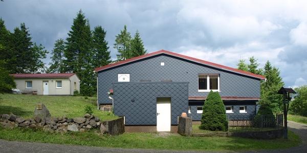 Ankunftsansicht: Vorne die verkleidete Wetterseite der Hütte, hinten links die Ferienwohnung.