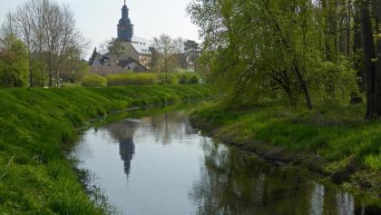 Die Laurentiuskirche von Trebur spiegelt sich im Schwarzbach