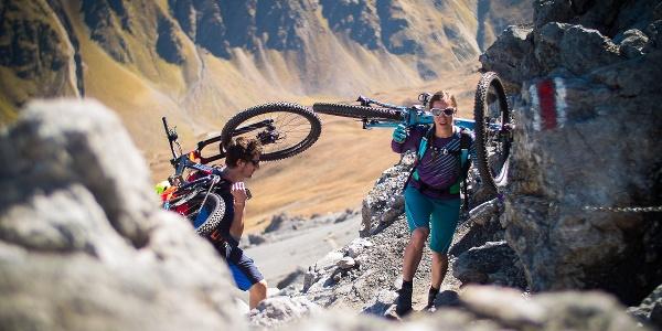 Zwei Mountainbiker schleppen Ihre Bikes auf den Piz Umbrail