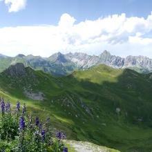 Blick von der Geißspitze zurück zur Bergstation Golmerbahn über weite Teile der Wanderstrecke (immer auf dem grünen Berggrat entlang aufsteigend). Rechts unten sind bei starker Vergrößerung auch Teile des Hinwegs zu sehen.