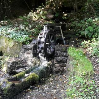 Brunnen mit kleinem Wasserrad an der Wanderbahn