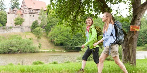 Wanderer auf dem Jagststeig vor Schloss Rechenberg