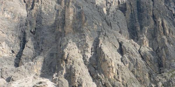 Wandbild; der Einstieg befindet sich am Ende der Wiesen und der Schotterrinne zwischen den beiden plattigen Pfeilern