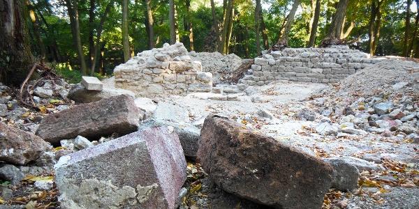 Előtérben szabályosan megmunkált építőkövek, háttérben megmaradt falrészletek