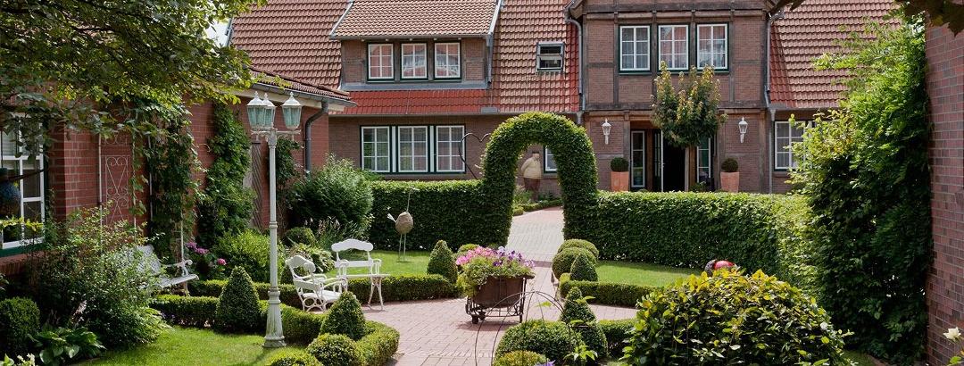 Gäastehaus des Hotels im Altländer Stil, Blick auf den idyllischen Innenhofbuchsbaumgarten