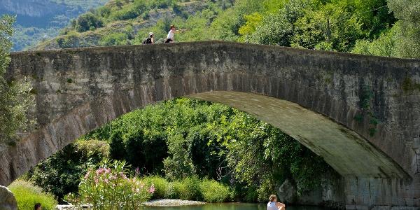 The Roman Bridge in Ceniga with the small beach on the river