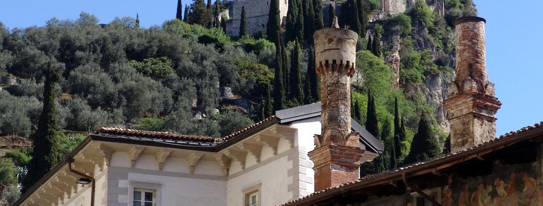 I comignoli di Palazzo Marchetti, sullo sfondo il castello di Arco