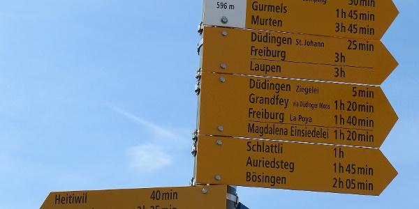 Wegweiser am Bahnhof Düdingen.