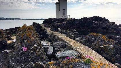 Carraig Fhada lighthouse and narrow path out to the lighthouse across the rocks