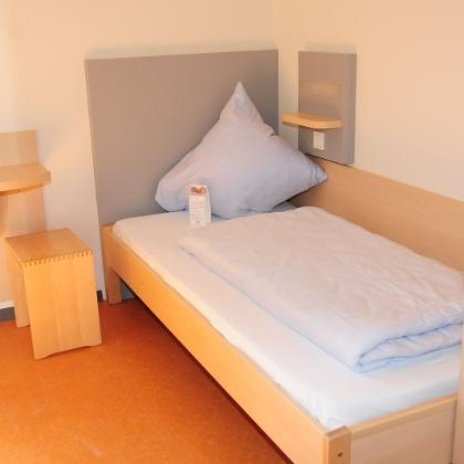 Einbettzimmer mit Nachttisch und Schrank