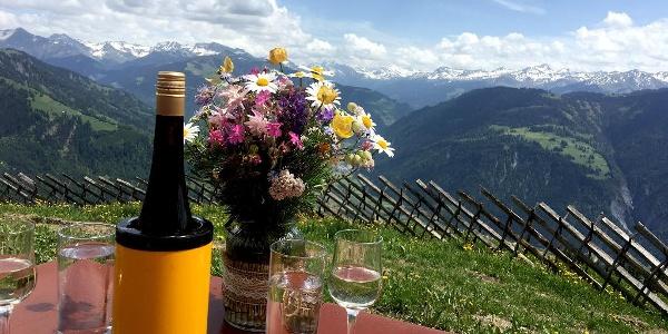 Stilbild in Maiensäss Valcaus: Mit einem feinen Weisswein aus der Bündner Herrschaft und einem Bergblumenstrauss.