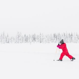Child skiing on a ski track in Ruka