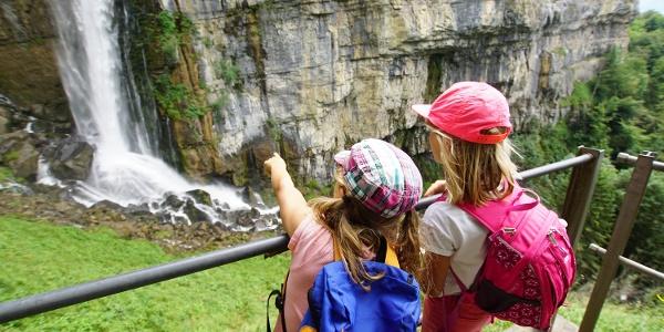 Kind zeigt auf den Wasserfall