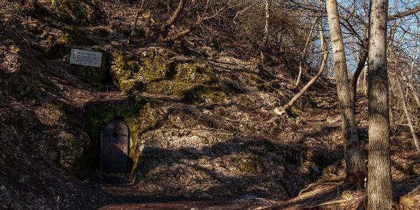 A Bátori-barlang a Nagy-Hárs-hegyen, a bejárat felett az emléktáblával