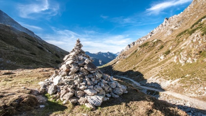 Stone pile waypoint at Preuneggsattel mountain saddle in Preuneggtal valley