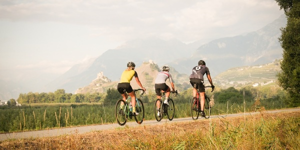 3 cyclists on the road with the castles of Sion in the background