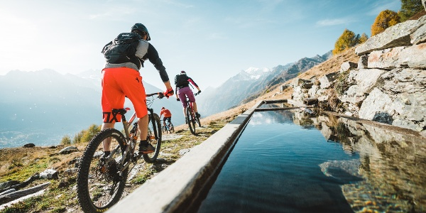 Mountain bikers ride near a pool on the descent to Giw.