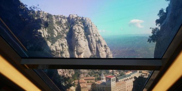 Das gläserne Dach der Standseilbahn ermöglicht bereits die ersten beeindruckenden Tiefblicke auf Das Kloster Montserrat.