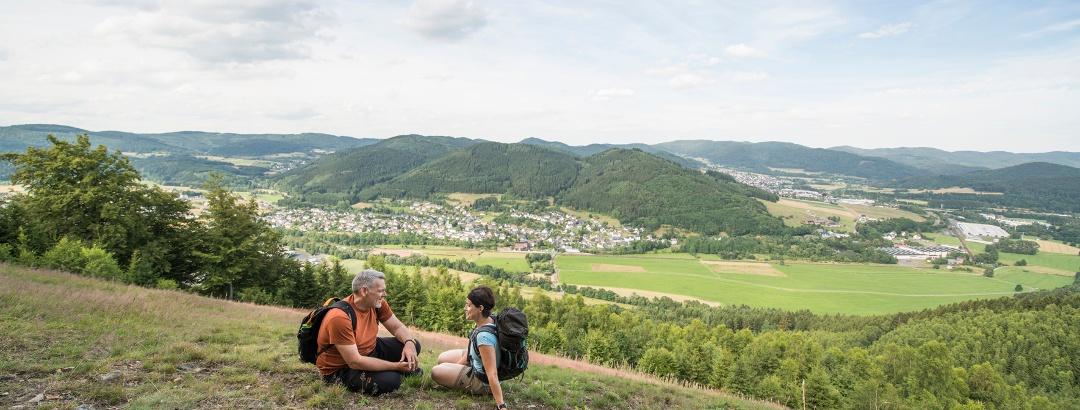 Zwei Personen rasten auf einem Berg_Ausblick auf das Tal