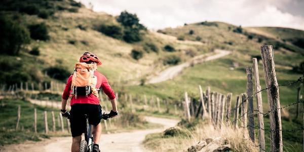 Mountain bike rider on country road, track trail in inspirational landscape