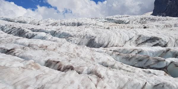 Überquerung des Gletschers mit Holzpfählen als Wegweiser