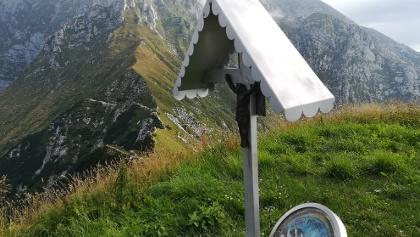 Gipfelkreuz des Mt. Guarda mit Mt. Canin-Symbol – dahinter die Wegführung in Richtung Baba Piccola