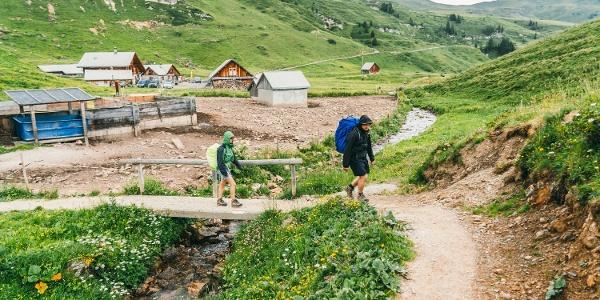 Der Weg führt vorbei an Blumenwiesen und Alphütten.