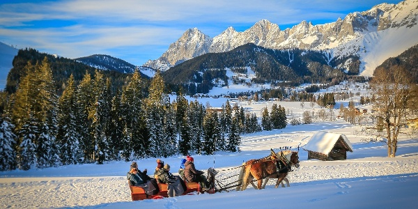On horse-drawn sleigh with terrific panoramic view to Dachstein massif