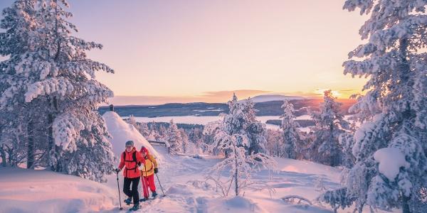 Lumikenkäilijöitä Jyppyrävaaralla, taustalla hieno maisema Ounasjärvelle ja Ounastunturin Pyhäkerolle