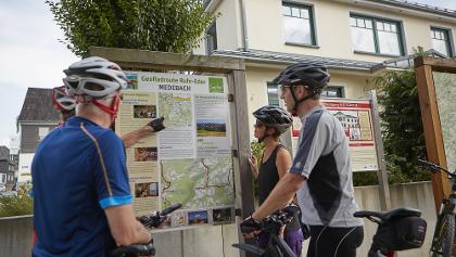 Radfahrerinnen und Radfahrer informieren sich in Medebach über den weiteren Streckenverlauf.