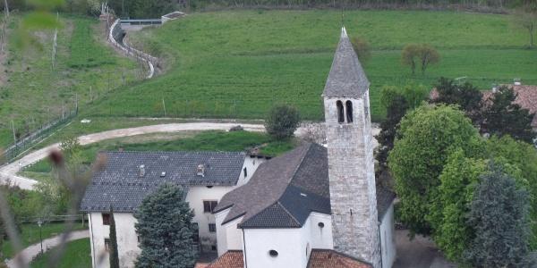 La chiesa della Madonna Assunta sorge isolata con sagrato panoramico sulla conca di Terlago.