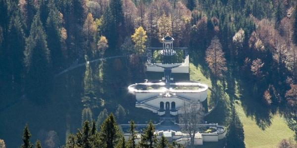 Tiefblick vom Gipfel mit dem Teleobjektiv auf den Park von Schloss Linderhof