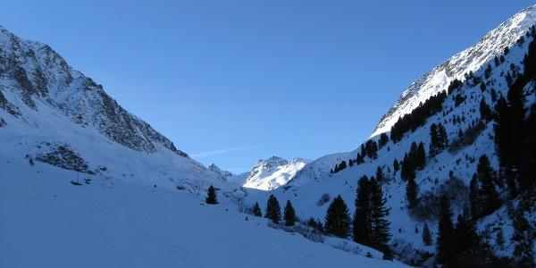 Dann weitet sich das Tal wieder. Hinten taucht das Gipfelziel in der Sonne auf.